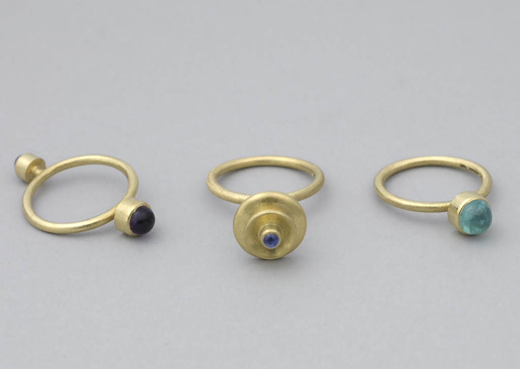 Matt-textured gold band with projecting decoration of small circular blue topaz cabochon surmounting two gold discs.