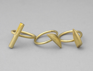 Matt-textured gold band decorated with canted gold cylinder having triangular groove.