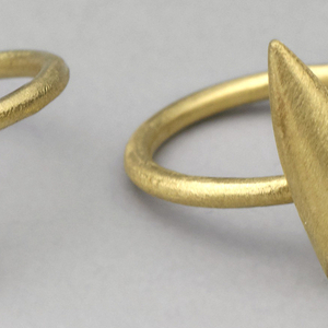 Matt-textured gold band decorated with gold bullet-shaped form.