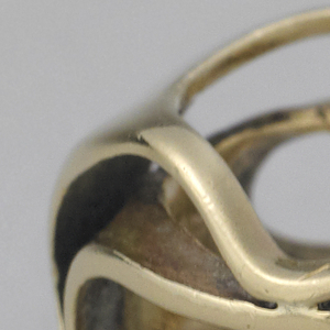 Roughly circular form of irregularly curved strands of gold with two narrow solid segments opposite eachother.