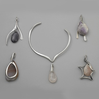 Pendant composed of pink ovoid stone in irregular five-pointed silver wire surround depending from silver loop.