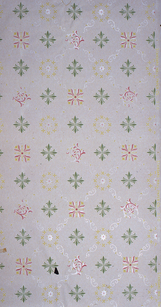 On gray ground, white scroll treillage with three motif variations: green foliate cross, yellow floral wreath, and yellow and red leaf-tulip motif.