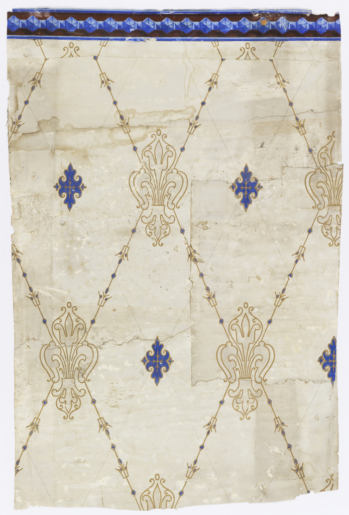 Diamond trellis design in metallic gold with blue accents, with fleur-de-lis motif at intersections. Smaller blue medallion in center of diamond.  Narrow border along top edge, containing blue center band on burgundy background.