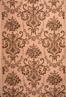 Repeating motif of bouquet of flowers in vase. The vase sits on a medallion, which are joined by foliage swags. Printed in brown on tan ground.