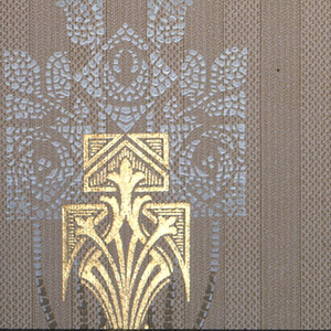 Central metallic gold motif. Above is a group of stylized white roses, printed in a mosaic effect. Background is a striped brown.