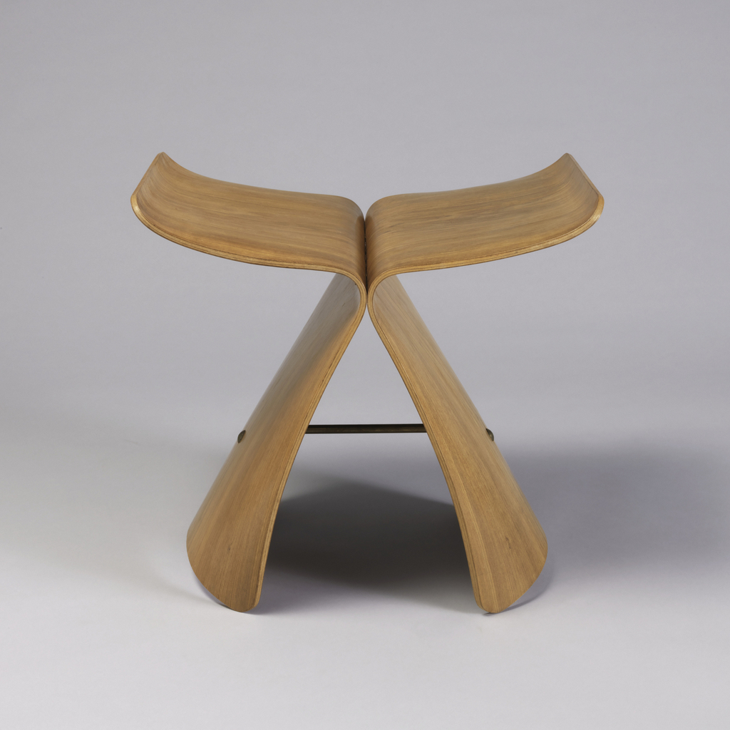 Form composed of two inverted, curved L-shaped plywood elements joined with brass fittings to form up-curved planar seat on splayed base; brass rod as stretcher in base.