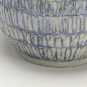 Ovoid body, with little flaring neck. Grayish paste, half-matte glaze. Rows of incised loops between horizontal lines, all filled with blue.