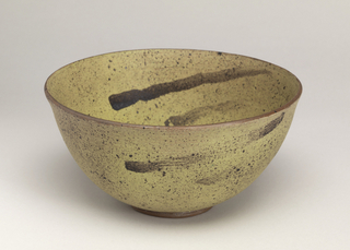 Curved, flaring body on slight foot. Matte chrome yellow glaze, with manganese brown steaks and specks. Rim and foot unglazed.