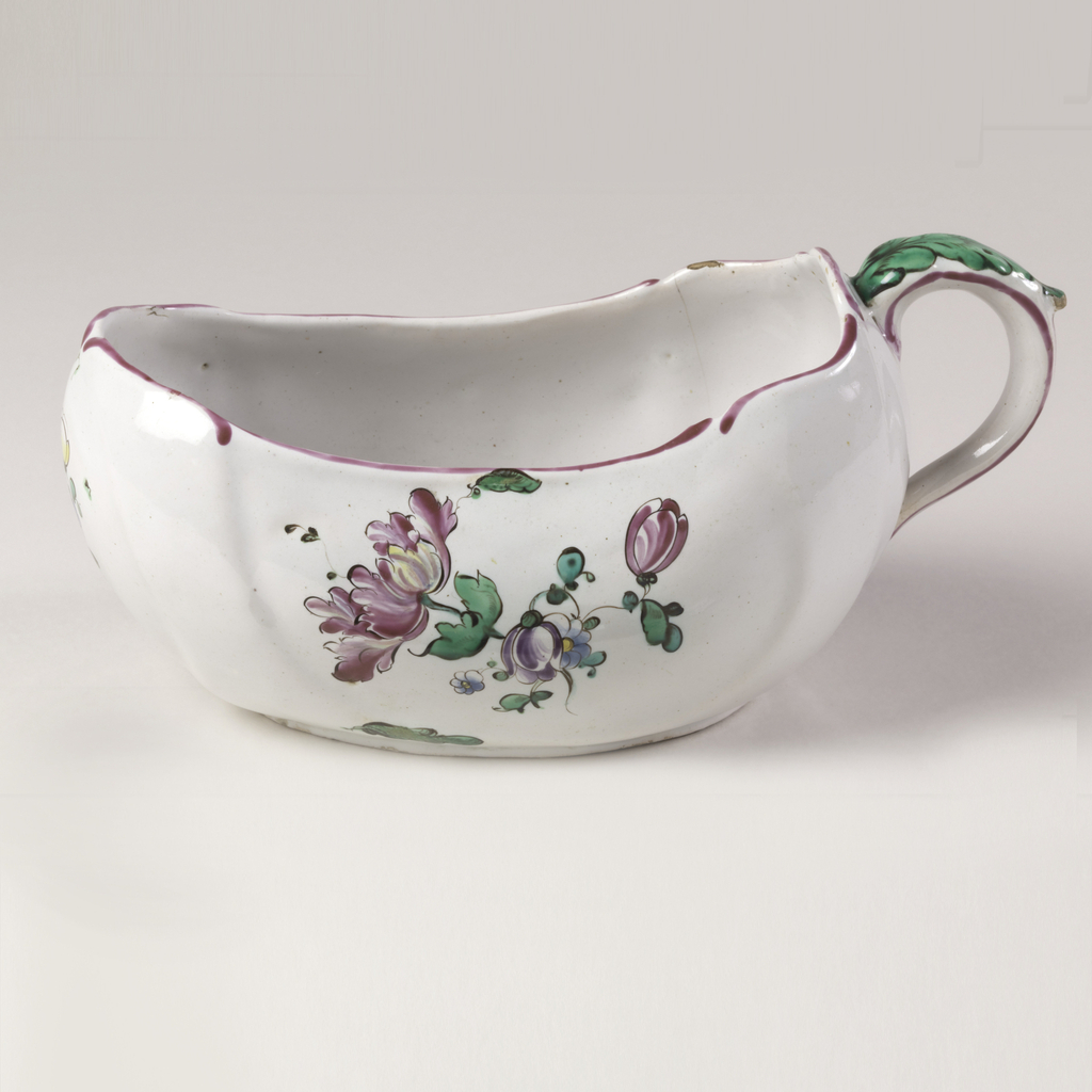 Oval boat-shaped vessel with indented sides and handle at high back end. Contoured rim edged in red. Handle topped by green leaf. Pink-white ground with sprays of flowers.