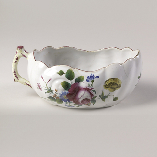 Oval boat-shaped vessel with contoured rim outlined in red. Rustic handle washed with yellow and decorated with red. Sprays of red, blue and yellow flowers with green leaves on sides and front.