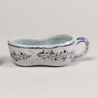 Long vessel with handle at one end. Tinted blue glaze on warm beige earthenware. Body painted with blue and red leaves. A shaky blue and red line under the rim. Lines and leaf patterns break at handle which is decorated with blue leaf motif and spirals.