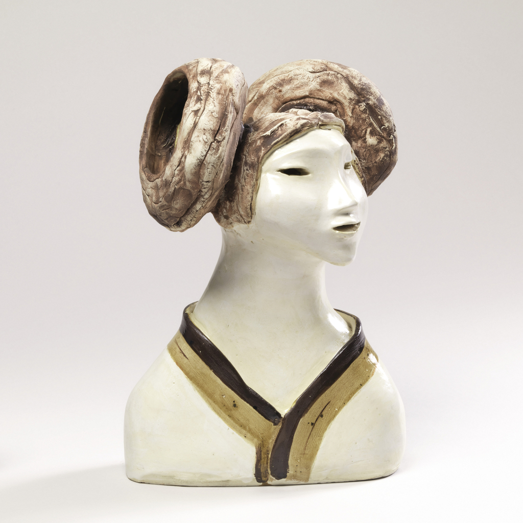 Bust of a woman down to shoulders with head turned to the side and down. Her hair is parted at center and swept up into two large buns.