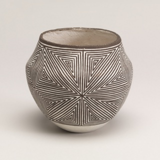 The globular body of the pot rests upon a flat base.  The swelling sides have a slightly angled shoulder; the body tapers toward a circular mouth.  The exterior is painted in a traditional geometric line pattern of a repeating series of interlocking continuous lines arranged in contiguous triangles.