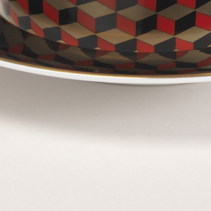 Slightly flared cup with 3-dimensional checkerboard pattern in red, gold, and black squares. One cube is painted inside white cup interior. Hexagonal handle in gold.  Saucer with bright white well; border in black with gilt rim.