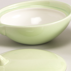 Lime green bowl with paddle handle and round lid set into mouth of bowl, with paddle handle that extends from side of lid.