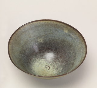 Footed stoneware bowl with gradient color in blues, grays and yellow. Rim is in brown; interior has small spiral design.