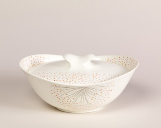Oval bowl with inner rim for lid to rest on and extended lips where floral pattern of orange and pink dots are painted. Side of dish is decorated with black lines and orange and pink dots. Oval lid with spattering of pink and orange dots along long sides with cleat-shaped finial.