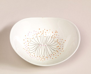 Oval bowl with lifted sides, decorated with black lines, pink and orange dots on off-white ground.