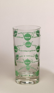 "Tall, cylindrical; with green enamel repeat decoration of teapots and inscription ""The Tea Center."""