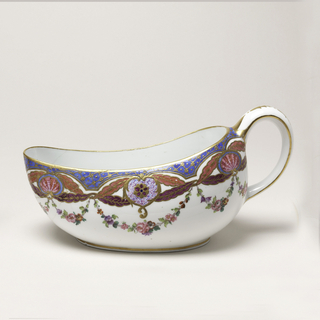 Boat-shaped vessel, one end higher than the other; vertical handle at high end. White ground with gilt rim, below which is gilt diaper patterns on blue. Beneath this area are rose and mulberry-colored swags with centered shell and rosette motifs, all with gilded outlines and details. Floral festoons hang from swags. Gilding on handle and around base.