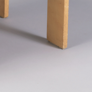 Rectilinear stool formed of single piece of birch plywood cut and bent to form two legs on one side, third leg opposite,with seat curved up at ends.