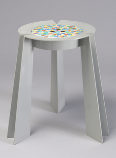 Gray, three-legged thin-walled molded plastic form with circular seat having inset circular fiberboard panel with hand-painted decoration of overlapping multi-colored 'dots' (brush strokes) on white ground; three finger holes in center of seat panel allowing it to be lifted out, revealing shallow storage area.