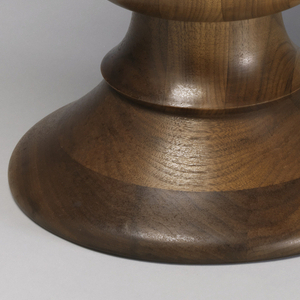 Baluster-shaped wood form with slightly indented circular seat and low, broad conical base.