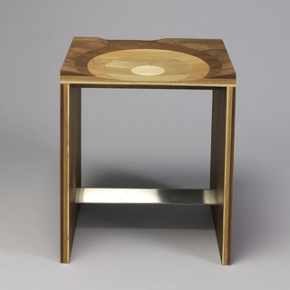 Rectilinear form; square seat of laminated black walnut, mahogany, cherry, oak, ash woods arranged in concentric circles and carved to form circular indentation; base formed by two laminated walnut panels with bent sheet metal stretcher.