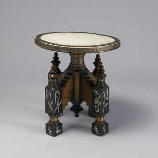 Circular vellum seat with stamped brass surround on intricate base with central column and four stepped, block-like legs with inlaid white metal foliate and caligraphy-like designs; brass banding at feet and finials.