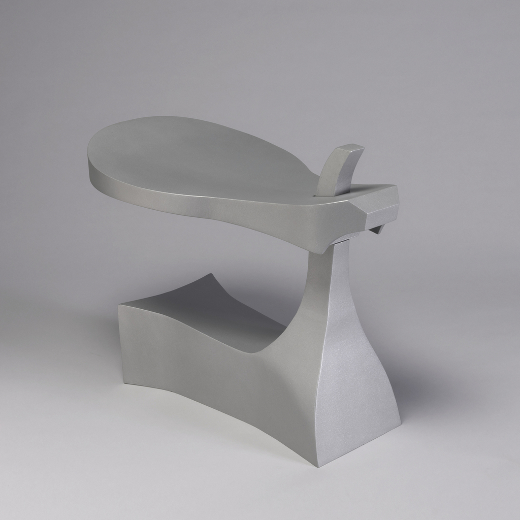 Aluminum form composed of removeable saddle-like seat on tapering post at front of broad, curving, block-like base.