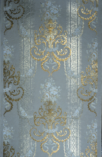 On blue ground, silvery vertical bands and staggered anthemion motifs in gold and gray.