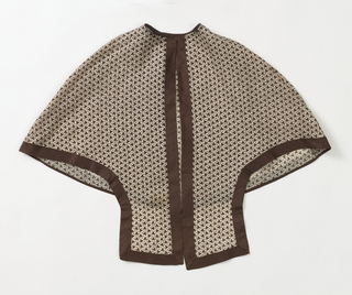 Woman's capelet with jewel neck and squared tabs in front. White cotton with small-scale all-over pattern of circles and three-lobed forms in brown; with dark brown binding on all edges.