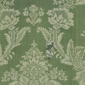 Stylized symmetrical repeat of floral palmette in continuous ogival framework of flowers and leaves in white on a green twill ground. Two striped green and yellow selvages.