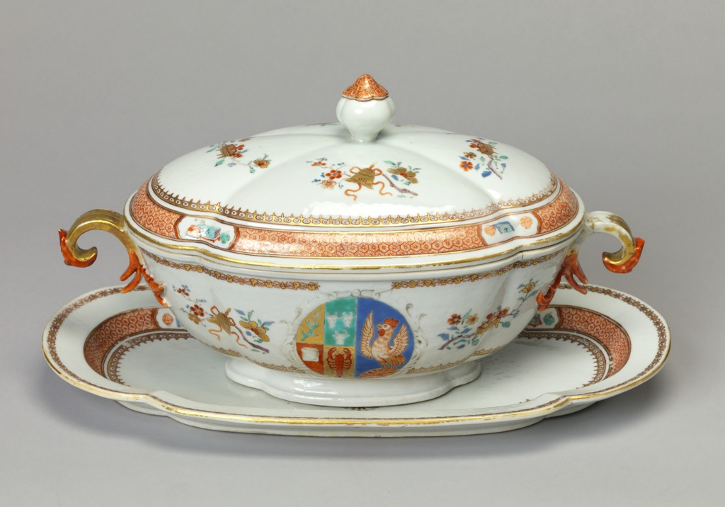 A tureen, lid and stand decorated in gilt with red details. Depicted on the set are small flowers and an emblem with a chicken, lobster, and other items. Arms are those of the Scholten family of Amsterdam who were in the grocery business.