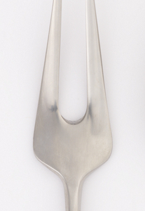Integral. Oval bowl, concave, with two tapered tines. Shoulder with flat edge. Handle flat, tapered with curved elliptical end, slightly upturned.
