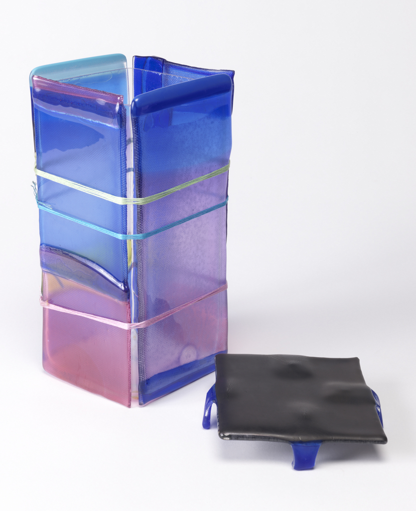 Vase consists of applied mutlicolored sheets of glass in blue, pink, yellow, purple and black cast glass lid.