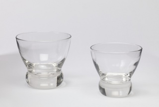 Clear circular glass tapered at the bottom with thick bulbous base.