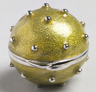 Spherical container hinged to open along center, surface of light green enamel studded with tiny bead-like  protrusions. Solid perfume contained inside.