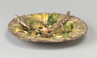 Oval deep-rimmed platter with ground of mottled brown, green, and blue glaze; decorated with applied  naturalistic leaves, shells, snails, and lizards.