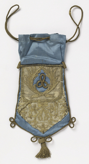 Bag probably made from pieces of older textiles. Blue silk edged with silk cord and a tassel with appliquéd pieces of metallic cloth with embroidery.