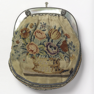 One side of purse is canvas, embroidered in colored silks with a basket of flowers. The other side is purple velvet. Mounted on a silver frame with mother-of-pearl inlay. Lined with pink silk.