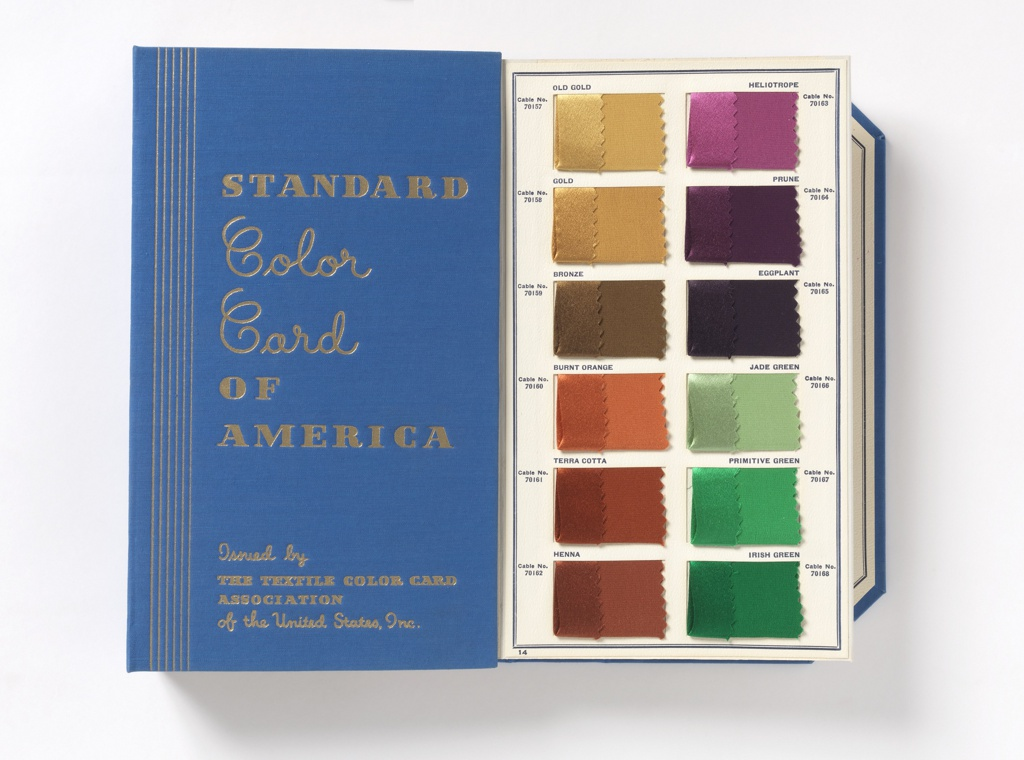 Book with thick accordion-folded pages containing two-hundred and sixteen dyed silk color samples. Each sample is folded to show the dye color on both satin and crepe weave.  Each color has a name and a cable number.