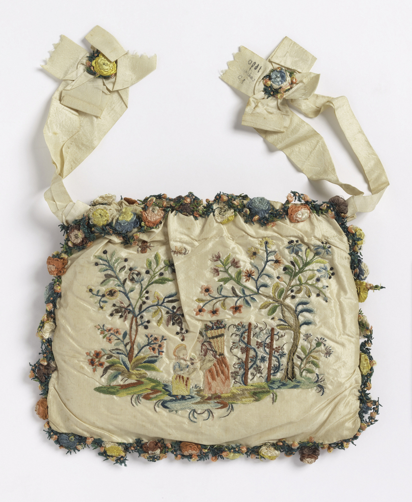 """Woman's bag of white taffeta, embroidered in colored silks, metal thread and sequins. On one side, children playing game of """"la main chaude;"""" on the other, woman offering grapes to a child. Faces painted. Edged with elaborate trimming of silk flowers."""