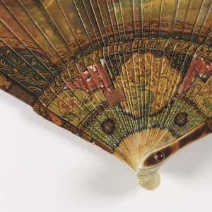 Brisé fan. Bone sticks painted to resemble vernis martin. Obverse: musical group in a landscape, chinoiserie scene at gorge. Reverse: a rural landscape with a church spire. Rivet is set with a ruby-colored stone. Tortoise shell on guards.