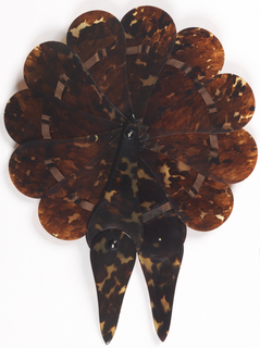 Cockade fan. Paddle-shaped tortoise shell sticks that open to a full circle. Front and back sticks pivot down to form a handle. Tortoise rivet heads with metal rivets. Brown silk ribbon does not appear to be original.