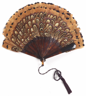 Brisé fan with dark and light brown feathers mounted on faux tortoise shell sticks. Silk connecting ribbon and tassel.