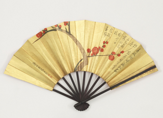 Pleated fan with a printed gold paper leaf showing a stylized cherry blossom and loose Japanese writing in black and red. Wood sticks painted black.