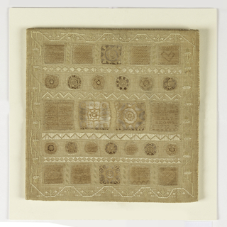 Small square sampler of fine white linen with five rows of squares and circles cut out, with needle lace and hollie point fillings. White geometric bands in between the rows, and a border of acorns in curving vine.
