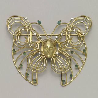 Brooch in butterfly shape made of thin gold wire pieces, with face of woman and hair coiled into butterfly's wings; small diamonds throughout.