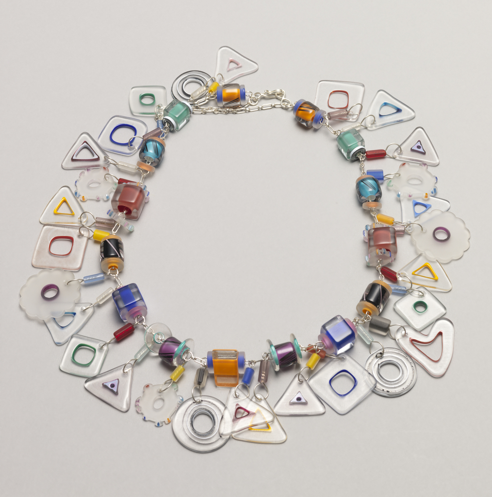 Colored and clear glass charms in various geometric shapes linked by silver chain; hook and loop and safety chain.